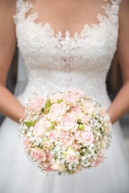 Braut mit Brautstrauss aus Rosen und Schleierkraut