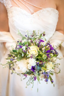 Braut mit wildem, natürlichem Brautstrauss in den Farben blau und weiss