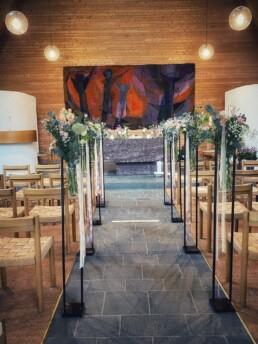 blumige Gestaltung mit Metallständer bei Bankreihen Kirche